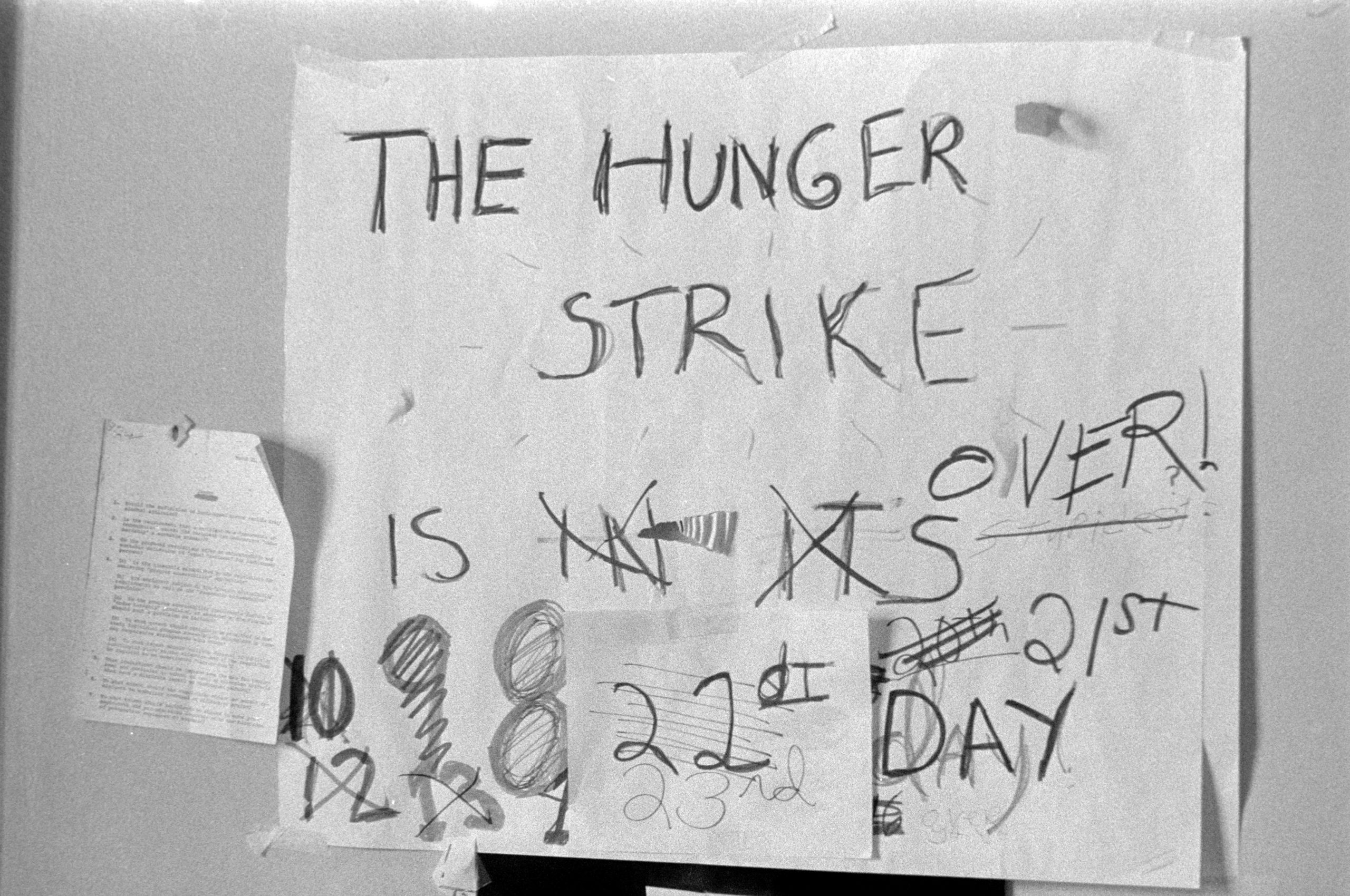 "A sign counting the days of a hunger strike. The length of the hunger strike was updated, reaching up to the 23rd day. This has all been crossed out and the sign now reads ""The hunger strike is over""."
